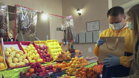Young couple with protective mask and gloves chooses a fresh tangerines, puts Live Action