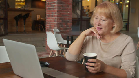 Happy senior lady watch funny video on notebook in cafe Live Action