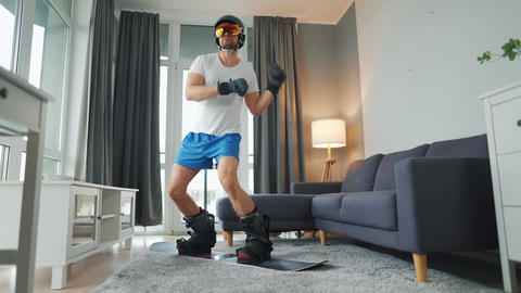 Fun video. Man in shorts, t-shirt and snowboarding equipment happily dancing and Live Action