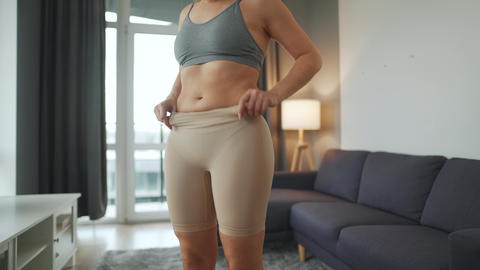 Woman puts on slimming underwear to improve body silhouette Live Action