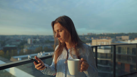 Woman starts her day with a cup of tea or coffee and checking emails in her Live Action