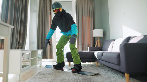 Fun video. Man dressed as a snowboarder rides a snowboard on a carpet in a cozy Live Action