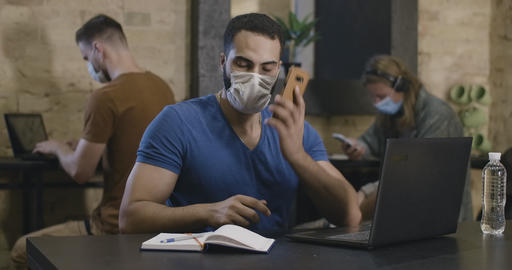 Portrait of confident Middle Eastern man in Covid-19 face mask typing on laptop Live Action