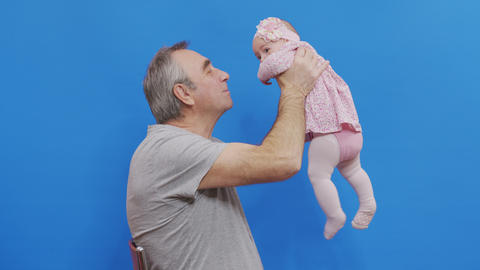 Senior man talking to his baby granddauther, holding her in the air, close up Live Action
