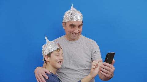 grandfather with his grandson in protective foil hats from 5g radiation standing Live Action