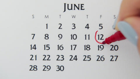Female hand circle day in calendar date with a red marker. Business Basics Wall Live Action