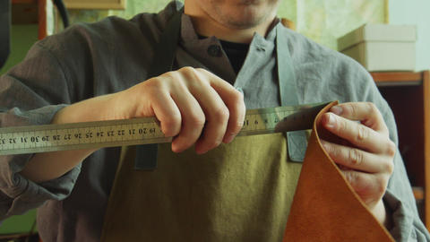 A shoemaker uses a steel ruler to measure out the piece of leather needed to Live Action