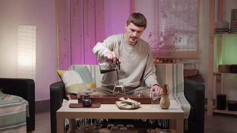 A middle aged man holding a teapot of brewed tea high pours the drink into a Live Action