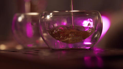 Two glass bowls are filled with a stream of tonic Chinese tea from a teapot at a Live Action