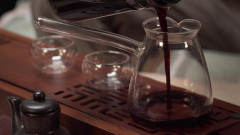 The master of the tea ceremony pours the brewed tea from the teapot into a jug Live Action