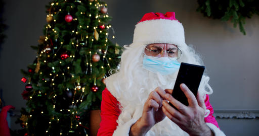 Santa claus with medical mask in living room and chatting by smartphone with Live Action