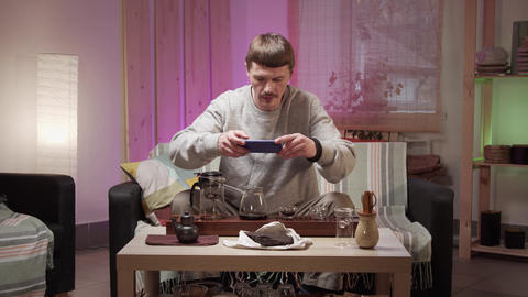 An adult man in his apartment arranged a tea ceremony and photographs a set of Live Action