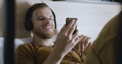 Portrait of young positive man in headphones using video chat. Cheerful handsome Live Action