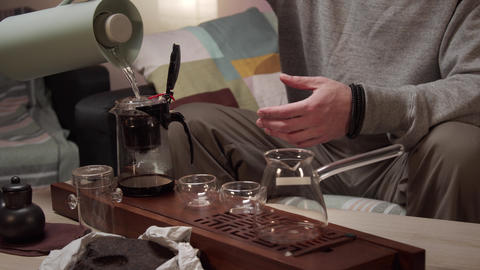 Unrecognizable man pours boiling water from a thermos into a teapot with tea Live Action