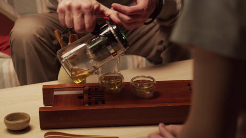 Two friends enjoy natural Chinese tea at a home tea ceremony and communicate Live Action