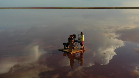 Aerial view on a band floating on a raft in the sea, performing, reflection, 4k Live Action
