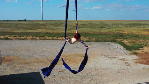 Aerial silks outdoors, amazing performance by an athletic woman, sunset, 4k Live Action