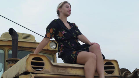 Barefoot blonde woman sits on an old tractor Live Action