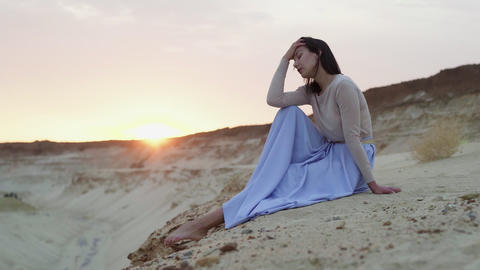 Beautiful young woman in blue skirt sits on top of sand hill with sunset on Live Action