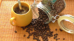 Yellow coffee cup and the cup is around coffee beans Live Action