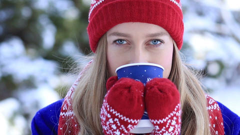Young woman enjoying scent of coffee in wintertime Footage