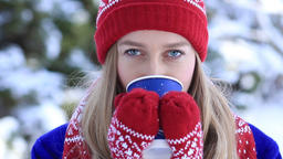 Beautiful woman drinking hot coffee in winter park Footage