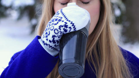 Woman drinking hot wine from thermocup in winter Footage