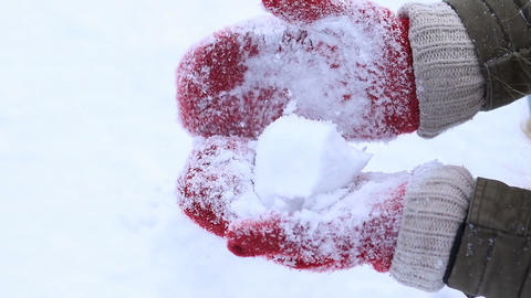 Female hands in knitted mittens making snowball Footage