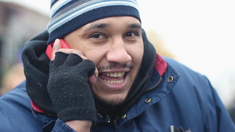 Happy male immigrant wearing shabby work clothes having phone conversation Footage