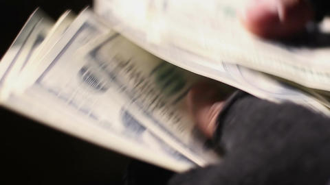 Closeup shot of male hands in shabby fingerless gloves counting cash in dollars Footage
