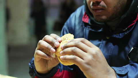 Man eating burger at fast food restaurant, unhealthy diet dangerous to health Live Action