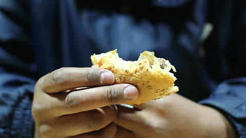 Miserable pauper eating leftover burger, man suffering from hunger and poverty Footage