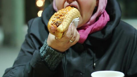 Middle age lady eating cheap street snack, addicted to high calorie junk food Footage