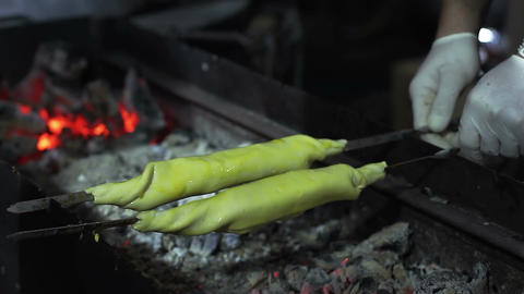 Street vendor cooking traditional cuisine dish on charcoal grill, food festival Footage