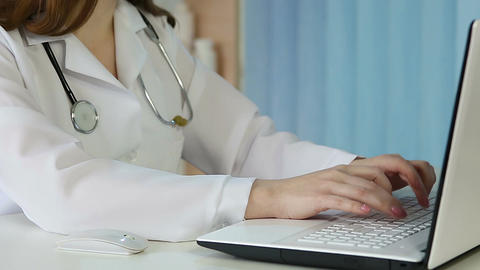 Woman doctor browsing pages on laptop, typing letter, consulting patients online Footage