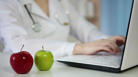 Female M.D. working in office, typing on laptop. Apples on table, healthy eating Footage