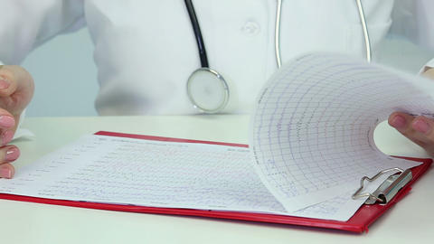 Doctor examining electroencephalogram, studying patient's brain activity, EEG Footage