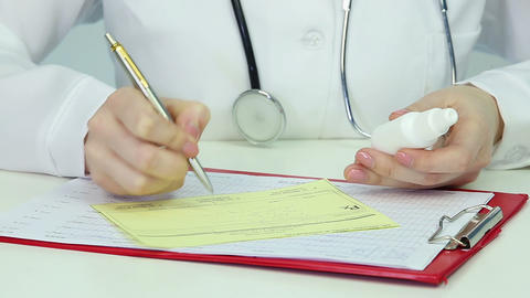 Physician prescribing medication, filling out prescription form. Reception hours Footage