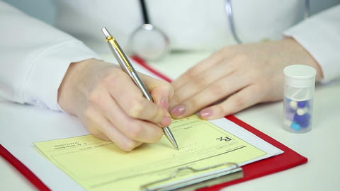 Close-up of physician's hands writing medical prescription, refilling medication Footage
