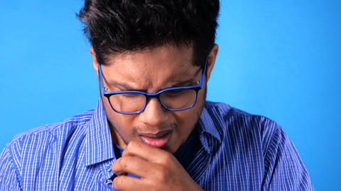 young man coughing and sneezes on blue background Live Action