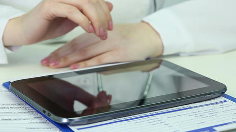 Woman doctor using tablet PC, checking electronic medical records, consultation Footage