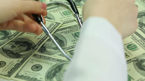Doctor's hands lay stethoscope on dollars. Corrupted health care system, bribery Footage