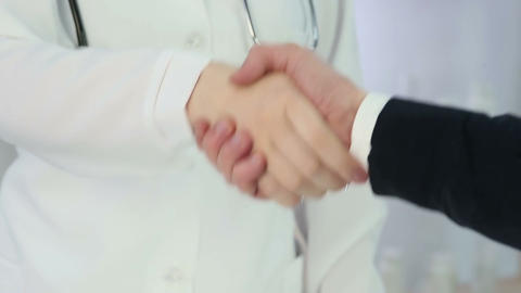 Grateful patient and qualified doctor handshake, healthcare services at clinic Footage