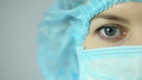 Close-up shot of female medical worker wearing face mask looking into camera Footage