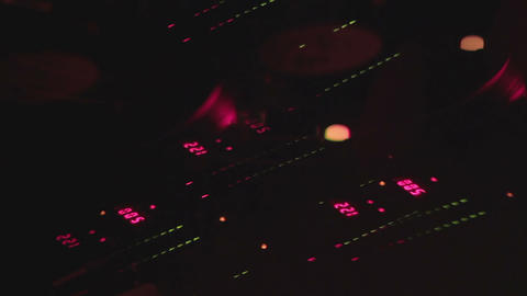 Hands switching controls on console, DJ mixing music at party in night club Footage