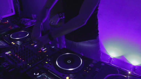 Skilled DJ twisting controls on sound board, playing music in night club, party Footage