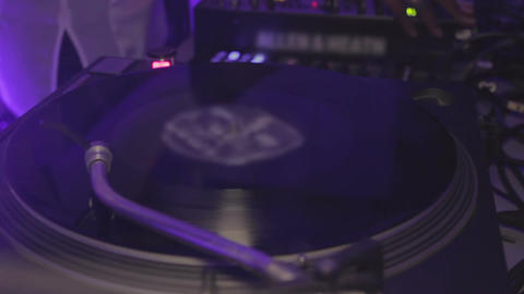 Dj playing music at night club. Vinyl record spinning on the turntable. Party Footage