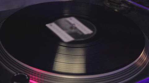 Vinyl record playing and turning around. Night club atmosphere, entertainment Footage