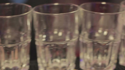 Barman putting ice cubes in glasses, serving drinks at party in the night club Footage