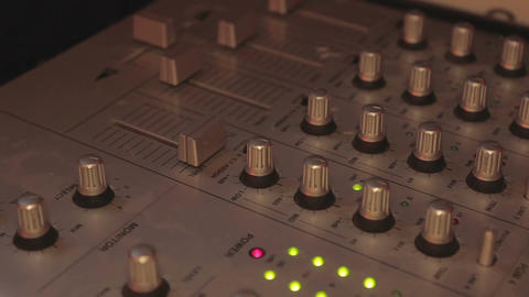 Close-up of deejay's hands playing cool music and pushing mixer buttons. Party Footage